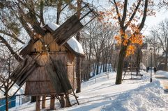 Postcard with windmills in winter. The Village Museum in Bucharest located on the side of Herastrau lake is an open-air collection of several dozen homesteads Royalty Free Stock Image