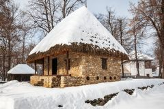 A stone cottage with a thatched roof covered in snow Stock Photo