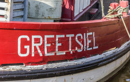 Village name on a red wooden fishing boat in Greetsiel. Germany stock photography