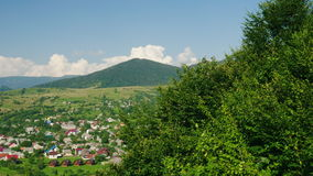 A village near the river. Against the background of the mountains covered with forest. Ski resort in summer, rest in the. A small village near the river. Against stock video