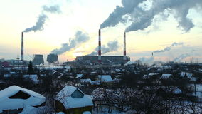 Village near termal power station at sunset. Thermal station smoke in sky at winter sunset in Russia stock video