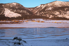 Village nearby the frozen lake Stock Image