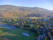 Village neighbourhood. Aerial view of a small village neighbourhood surrounded by large mountains Royalty Free Stock Photos