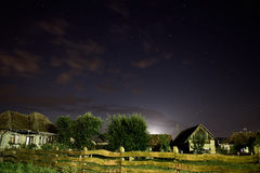 Village at night. Rural landscape at night with visible stars on a slightly cloudy sky Royalty Free Stock Image