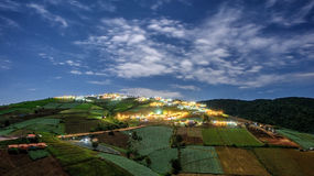 Village night scene with houses on hill Royalty Free Stock Photography