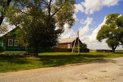Village old wooden rural houses with sloping roof beside the green grassy glade, trees and the road. Russia. Village of old wooden rural houses with sloping Stock Image