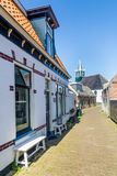 Village Oudeschild on Texel island in the Netherlands. Village Oudeschild with a row of trraditional fisherman houses and an old church on Texel island in the royalty free stock image