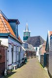 Village Oudeschild on Texel island in the Netherlands. Village Oudeschild with a row of trraditional fisherman houses and an old church on Texel island in the royalty free stock photos