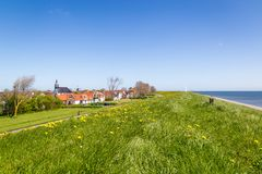 Village Oudeschild on Texel island in the Netherlands. Panorama Village Oudeschild with Martinus church, windmill and trraditional gable houses on the Wadden royalty free stock photo