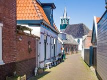 Village Oudeschild on Texel island in the Netherlands. Village Oudeschild with a row of trraditional fisherman houses and an old church on Texel island in the stock photography