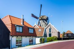 Village Oudeschild on Texel island in the Netherlands. Village Oudeschild with windmill and trraditional fisherman houses on Texel island in the Netherlands royalty free stock images