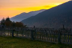 Village outskirts in mountains at dawn. Wooden fence along the road with puddle. deep autumn weather stock image