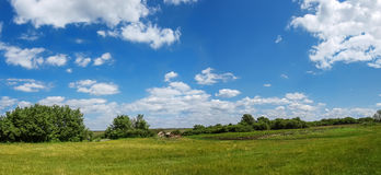 Village panorama spring - spacious green meadow, blue sky with c Stock Photo