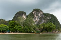 Village in Phang Nga Bay, Thailand. A typical Thai village in Phang Nga Bay, with beautiful limestone mountains rising in the background Royalty Free Stock Image