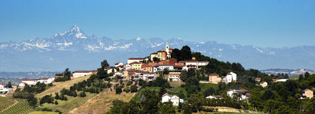 Village in Piedmont. Scenic view of village on hillside with Alps mountains in background, Piedmont, Asti, Italy Stock Photo