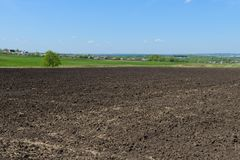 Village and a plowed field. Rural landscape with a village and a plowed field stock image