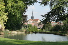 Village pond and Church. French Village pond and church on summer afternoon Stock Photo