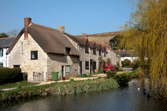Village pond and houses in Sutton Poynz in Dorset. Traditional, British, picturesque village in Dorset, England with pond, ducks and vintage buildings on a sunny Royalty Free Stock Photos