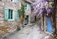 Village of Provence: cascading purple wisteria vine Royalty Free Stock Images