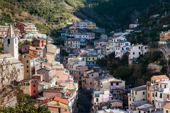 Village of Riomaggiore town with houses, located between mountains at Cinque Terre national park, Italy Stock Photos