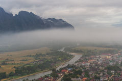 Village with river and mountain in mist Stock Photo