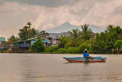 A Fisherman in the boat. A village by the river in Sarawak, Kuching, Malaysia Stock Images