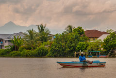 A Fisherman in the boat. A village by the river in Sarawak, Kuching, Malaysia Royalty Free Stock Image