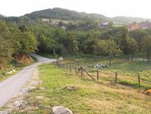 Village road to nowhere. Somewhere in Serbia with view of hills and green trees stock photo