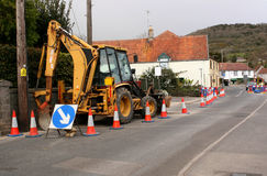Village road works. Back hoe and road works in the village of cheddar, somerset Stock Images