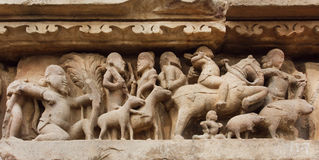 Village and rural people with animals on stone relief of Khajuraho temple, India. UNESCO Heritage site Stock Photos
