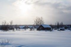Village russe traditionnel dans l'hiver pendant le coucher du soleil Photographie stock libre de droits