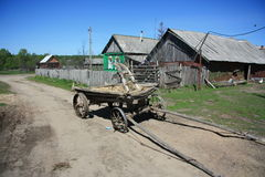 The village in the Russian outback. The village in the Russian outback. The cart with a plow. Royalty Free Stock Photography