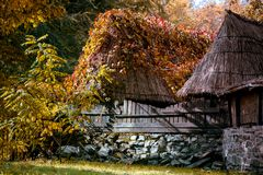 Village shacks with roofs of cane behind a wooden fence in autumn Stock Image