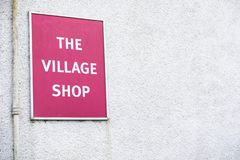 Village shop sign red on white wall background royalty free stock image