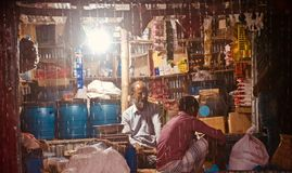 Village shopkeeper sitting in a shop in a rainy nights unique photo. People sitting around a village shop during the rain at night unique photo stock image