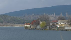Village on shore of lake during flooding. Houses at water`s edge of lake during flooding in early spring stock footage