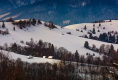 Village on snowy hill in winter. Lovely countryside scenery in mountainous region at sunrise Stock Photos