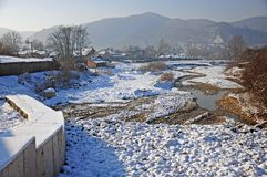 Village on snowy river valley Stock Images