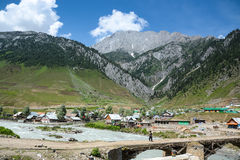 Village in Sonamarg, India among mountain range. Scenic view of village in Sonamarg, Jammu and Kashmir state, India among mountain range and river Royalty Free Stock Image