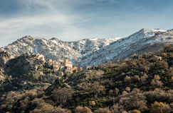 Village of Speloncato in Corsica with snow covered mountains Stock Photo