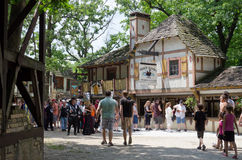 Village Square. A crowd of people in a village square surrounded by Elizabethan-era buildings at a Renaissance festival Royalty Free Stock Image