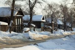 Village street in the snow. Wooden village houses stand in the snow along the road Stock Images