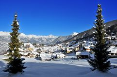 Village in swiss alps framed by pine trees Stock Photography