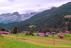 Village in the swiss Alps. In a valley, in the background are mountains with snow on a cloudy day Royalty Free Stock Photo