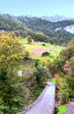 Village in the swiss Alps. In a valley with rural house, in the background are mountains on a sunny day.It´s a vertical picture Royalty Free Stock Image