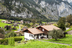 Village in the swiss Alps. In a valley with rural houses, in the background are mountains on a cloudy day Stock Image