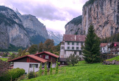 Village in the swiss Alps. In a valley with rural houses, in the background are mountains on a cloudy day Stock Photos