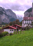 Village in the swiss Alps. In a valley with rural houses, in the background are mountains on a cloudy day.It´s a vertical picture Stock Photos