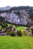 Village in the swiss Alps. In a valley with rural houses, in the background are mountains on a cloudy day.It´s a vertical picture Stock Images