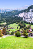 Village in the swiss Alps. In a valley with rural houses, in the background are mountains on a sunny day.It´s a vertical picture Stock Images